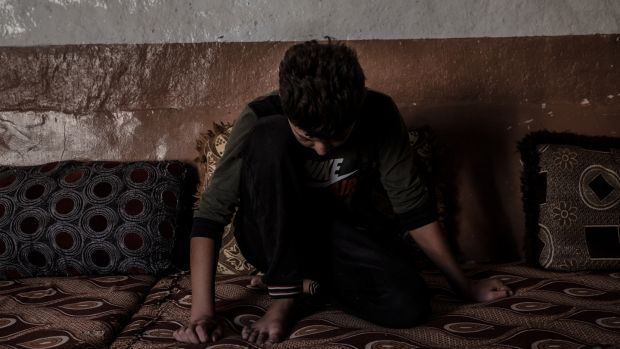 "A Yezidi boy (13) in his house in Sinuni. ""I feel lonely all the time. When I went to the hospital in Sinuni, I asked them to keep me there. I don't want to be home."" Photograph: Emilienne Malfatto"