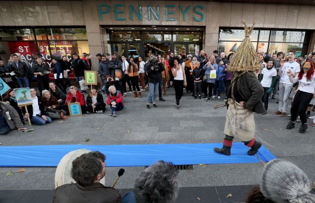 "REBELLION NOW THE FASHION? Protesters dressed as wren boys perform an impromptu ""fashion show"" outside Penneys on O'Connell Street in Dublin during an Extinction Rebellion (XR) demonstration. Fashion retailers have come under intense scrutiny in the last year from environmental activists. Photograph: Brian Lawless/PA Wire"