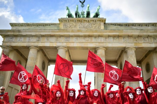 "FORETELLING OF THE APOCALYPSE: Red Rebel Brigade activists, part of the Extinction Rebellion global movement, perform in front of the Brandenburg Gate in Berlin, Germany. The climate-crisis movement has planned a ""spring rebellion"" this week, including marches aimed at blocking traffic in major cities. Photograph: Clements Bilan/EPA"
