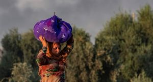 A woman carries her belongings over her head as she flees  Syria's northeastern town of Ras al-Ain   on October 9th. Photograph: Delil Souleiman/AFP/Getty
