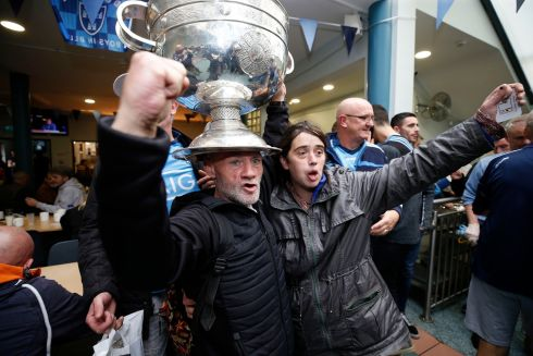 Paul and Haley Kelly with the Sam Maguire trophy during its Five in a Row visit to the Capuchin Day Centre on Bow Street in Dublin. Photograph: Nick Bradshaw/The Irish Times