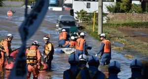 Rescue personnel use boats to evacuate people and care-givers from the Kawagoe Kings Garden elderly care centre in Kawagoe city, Saitama prefecture, on Sunday. Photograph: Kazuhiro Nogi/ AFP via Getty Images