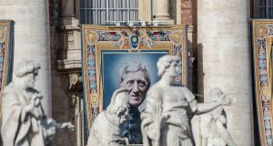A tapestry portraying Cardinal John Henry Newman hangs from the facade of St. Peter's Basilica, at the Vatican. Photograph: Alessandra Tarantino/AP