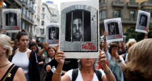 FACE OF SEDITION: A protester holds aloft an image of former Catalan vice-president Oriol Junqueras, mocked up behind bars, as hundreds of people blocked the central Via Laietana in Barcelona, Catalonia, Spain, demonstrating against prison sentences announced for Catalan pro-independence leaders. The Supreme Court condemned Mr Junqueras to 13 years in jail for sedition. Photograph: Quique Garcia/EPA