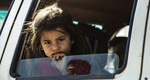 A young Syrian girl fleeing with her family from the northern Syrian flashpoint town of Ras al-Ain along the border with Turkey, peeks out of a car window as Syrian Arabs and Kurds moving away from the battle zone between Turkey-led forces and Kurdish fighters from the Syrian Democratic Forces (SDF), arrive in the city of Tal Tamr on the outskirts of Hasakeh on October 15, 2019.  (Photo by Delil SOULEIMAN / AFP)