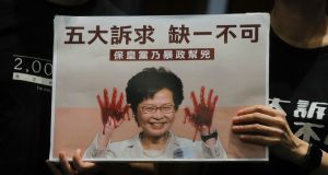 Pro-democracy MPs hold up a picture of Hong Kong leader Carrie Lam in the chamber of the Legislative Council in Hong Kong. Photograph: AP Photo/Kin Cheung