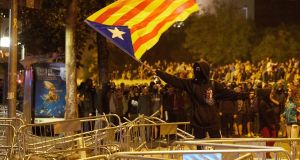 A demonstrator waves an Estelada, the unofficial flag used by Catalan independence supporters, during protests in Girona on Wednesday night. Photograph: David Borrat/EPA