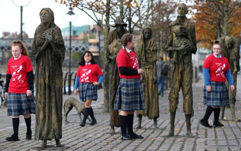 A CONSTANT REMINDER: Lia Sheridan, Laura Ashley Paulo, Chantelle Tunstead and Emma Whelan from Mount Carmel Girls Secondary School make their way through the Famine memorial statues on Custom House Quay in Dublin for the Commemoration for the International Day for the Eradication of Poverty, where they were performing. Photograph: Laura Hutton