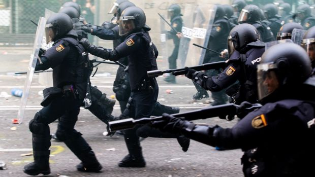 Spanish riot police members prepare to disperse protesters in Barcelona. Photograph: Enric Fontcuberta/EPA
