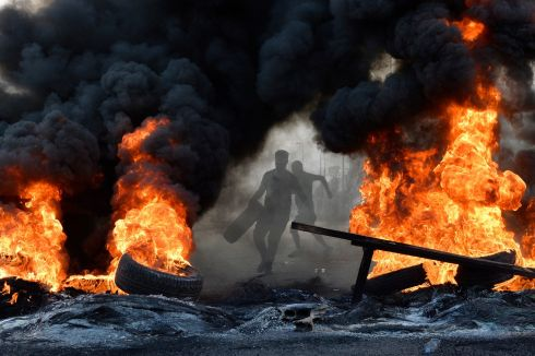 THROUGH FIRE: A protester throws a tire on a fire to block a Metn highway during a protest in north of Beirut, Lebanon. Protesters, mainly civil activists, started to demonstrate in downtown Beirut on October 17th, condemning the proposed taxes that would go along with the 2020 budget, especially an unexpected government plan to impose a fee of 0.20 cents a day for using WhatsApp calls. This charge will not make it through the government palace according to the Telecommunications Minister Mohamed Choucair after witnessing the impact this made on the streets. Photograph: Wael Hamzeh/EPA