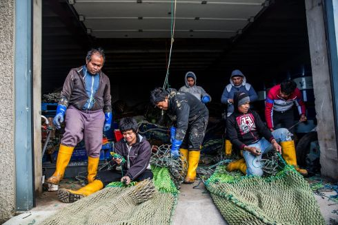 NETTED UP: Filipino workers Elmer Arquintill, Benji Bernisca, Randy Pepito, Roy Valencia, Mario Durans, Renato Decacion and Raynaldo Ogis  are seen repairing their fishing nets in Kilkeel harbor in Northern Ireland. Photo: James Forde/The Irish Times