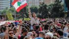 Protesters carry Lebanese flags and chant slogans in front the government palace during a protest in Beirut, Lebanon on Friday. Photograph: Nabil Mounzer/EPA
