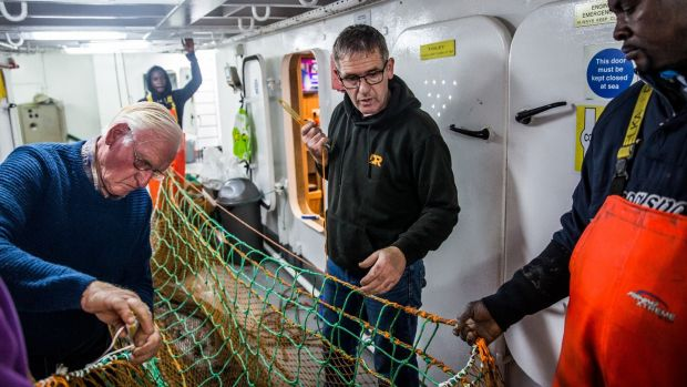 Philip Warnock, George Ado, Lawrence Warnock and Christopher Manah on the fishing boat Renown in Kilkeel harbour in Northern Ireland. Photo: James Forde for The Irish Times