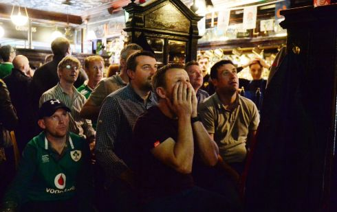 IT'S A ROUT: Irish rugby fans Michael Redmond (left, in Ireland jersey), Declan Cousins and Jimmy Murphy watch the Ireland vs New Zealand quarter-final match in the Rugby World Cup, in Doheny & Nesbitt pub on Baggot Street Lower, Dublin. Photograph: Alan Betson
