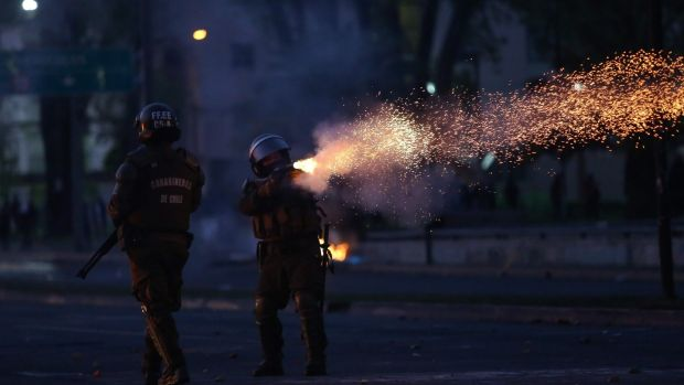 A riot policeman shoots tear gas during protests in Concepcion, Chile, on October 20th, 2019. Photograph: Pablo Hidalgo/AFP/Getty Images