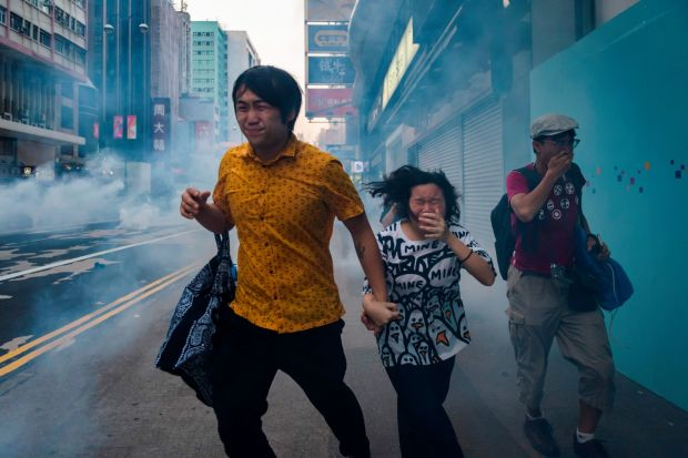 Protesters and bystanders along Nathan Road react from tear gas fired by police during the pro-democracy march in the Kowloon district. Photograph: Ed Jones/AFP/Getty