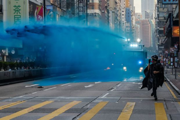 A protester runs from advancing police as they deploy a water cannon on a road in the Tsim Sha Tsui district in Hong Kong on October 20th. Photograph: Dale de la Rey/AFP/Getty