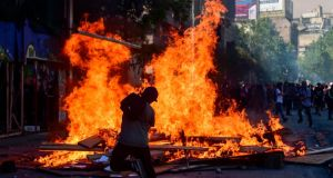 Demonstrators burn a barricade during a protest in Santiago, Chile on Monday. Photograph:  Martin Bernetti/AFP/Getty