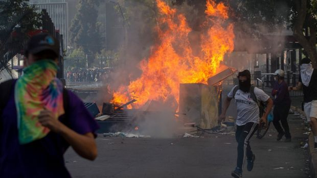 Demonstrators clash with riot police in Santiago, Chile. Photograph: Claudio Reyes/AFP/Getty