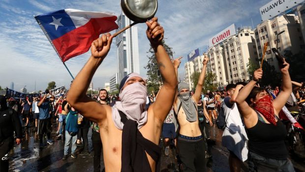 Demonstrators display flags and banners during a protest against Presidente Sebastian Piñera in Santiago, Chile. Photograph: Marcelo Hernandez/Getty
