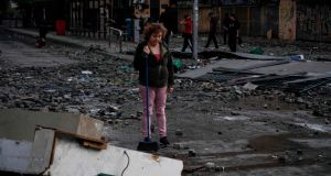 A  woman looks at a damaged street after clashes in Santiago on Monday. Photograph:  Pedro Ugarte/ AFP/ Getty