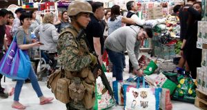 A military police stands guard at a supermarket as customers wait in line in Santiago, Chile. Photograph: Luis Hidalgo/AP