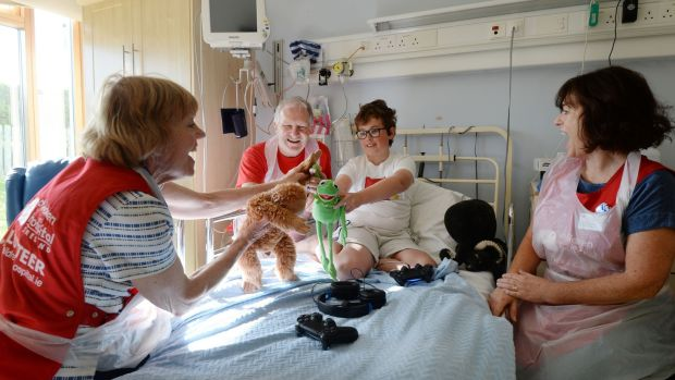 Volunteers Jacinta Nisbet, Ainnle O'Neill and Suzanne Lynch play with Matthew O'Connor (12) from Greystones, Co Wicklow, in Crumlin hospital. Photograph: Alan Betson