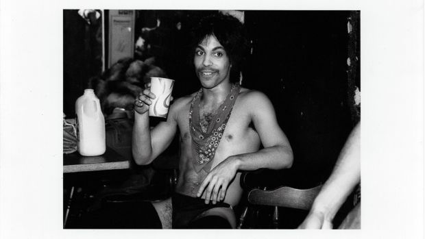 Prince sips some orange juice backstage during the Dirty Mind tour, 1981. Photograph: Allen Beaulieu