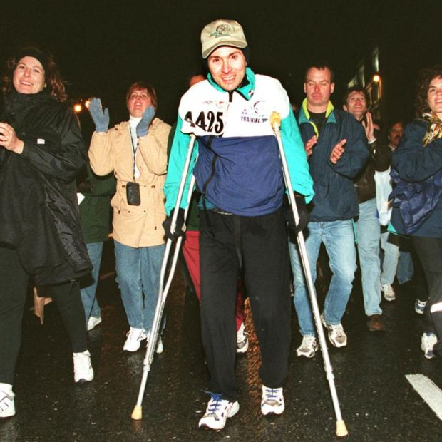 Stephen Le Rue from Chicago, surrounded by supporters as he crosses the finish line in 1998, after completing the marathon on crutches in just under 16 hours. Photograph: Eric Luke