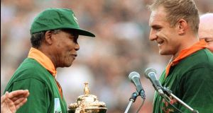 South Africa's president Nelson Mandela handing the William Webb trophy  to  South Africa's captain Francois Pienaar  in Johannesburg  in 1995. Photograph: Jean-Pierre Muller/AFP via Getty Images
