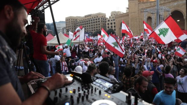A Lebanese DJ plays music as demonstrators wave national flags at the Martyrs' Square in the centre of Beirut. Photograph: Anwar Amro/AFP via Getty Images
