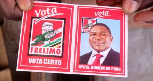 A local holds a card with a picture of Mozambique's president and leader of the Frelimo Party, Filipe Nyusi, ahead of  provincial and legislative elections, in Maputo, Mozambique on October 11th. File photograph: Grant Lee Neuenburg/Reuters