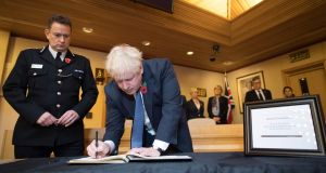British  prime minister Boris Johnson signs a book of condolence for the 39 people who died in a trailer. Photograph: Getty