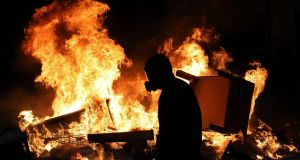 A masked anti-government protester stands by a burning street barricade in Santiago, Chile, Monday, Oct. 28, 2019.  (AP Photo/Rodrigo Abd)