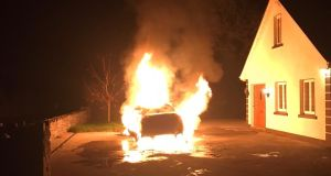 The car is seen on fire outside the family home. Photograph supplied by Brian Farrell