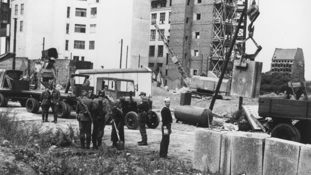 August 1961: East German military personnel supervising construction of the Berlin Wall. Photograph: Central Press/Getty Images