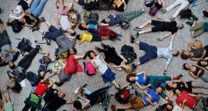 "Extinction Rebellion climate change activists lie on the floor as they perform a mass ""die in"" in the main hall of the Natural History Museum in London. Photograph:  Tolga Akmen/AFP"