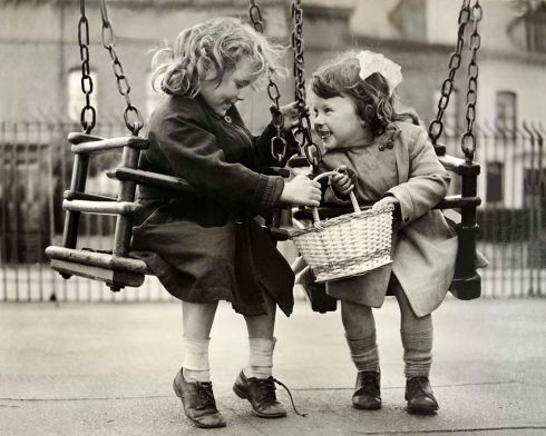 Two little girls on swings near Clifton Street in Belfast in the 1960s. At that time, none of us could have imagined how much life in the city would change over the next decades. Photograph: Stanley Matchett