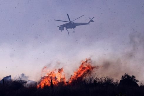 CALIFORNIA FIRES: A firefighter's helicopter drops water on the burning hills near the Ronald Reagan library as the Easy Fire spreads north of Los Angeles, California, US. Photograph: Etienne Laurent/EPA