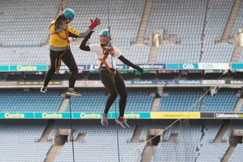 HIGH HOPES: Karen Mahon (yellow top) and Helen Keane take part in an abseil event at Croke Park in Dublin to raise funds for Alone. Photograph: Arthur Carron