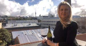 Mary-Therese Blair on her balcony in Auckland, New Zealand with the Sky Tower in the distance and a glass of wine in the foreground.