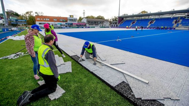 Volunteers help in laying the hockey pitch at Energia Park in Donnybrook ahead of the women's Olympic qualifier matches this weekend. Photograph: Morgan Treacy/Inpho