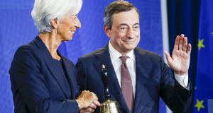 Christine Lagarde  accepts a ceremonial bell from outgoing president of the European Central Bank Mario Draghi. Photograph: Alex Kraus/Bloomberg