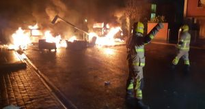 Two  cars alight and a fallen lamppost blocking the entrance to an estate in Fortunestown, Tallaght on Thursday night. Photograph: Dublin Fire Brigade/Twitter