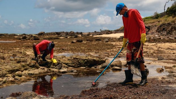 Volunteers help to clean up the oil sludge at the Itapuama beach, in Cabo de San Agostinho, Brazil. Photograph: EPA