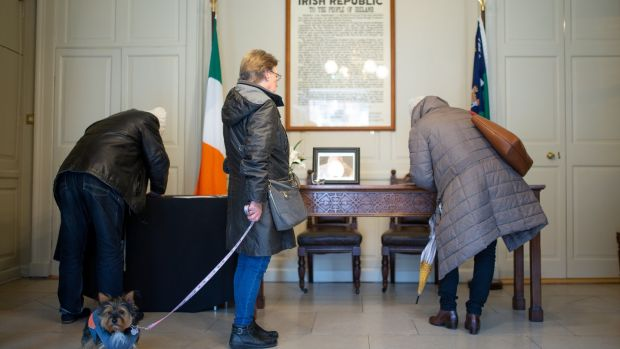 Helen Connolly, from Dublin, with her dog, waits to sign a book of condolence. Photograph: Tom Honan
