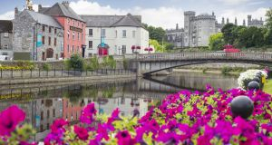 Flower lined riverside view of Kilkenny castle town and bridge