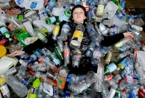 DON'T BOTTLE OUT: Beach cleaner Flossie Donnelly lies up to her neck in discarded single-use plastic bottles during a protest by Sick of Plactic campaigners at the Department of the Environment on Adelaide Road in Dublin. The campaigners want a deposit return scheme for plastic bottles and aluminium cans. Photograph: Alan Betson