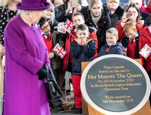TIME ON THEIR SIDE: Young boys watch as Queen Elizabeth arrives to bury a time capsule during a visit to the Royal British Legion Industries village, in Aylesford, Britain. Photograph: Richard Pohle/Reuters