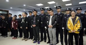 Defendants on drug charges standing with their handlers during a hearing at a court in Xintai, China's Hebei province, on Thursday. Photograph:  Office of China National Narcotics Control Commission/AFP via Getty Images